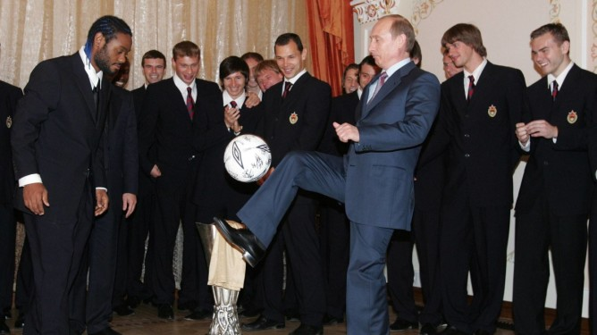 Russian President Vladimir Putin juggles a ball presented to him by soccer team CSKA as club's player Vagner Love, left, and other team members look on during their meeting in the Novo-Ogaryovo residence outside Moscow, Saturday, May 21, 2005. Putin congratulated soccer team CSKA for winning the UEFA Cup final. (AP Photo/Sergei Chirikov, Pool)
