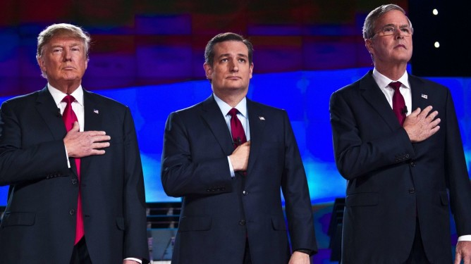 Republican presidential candidates (L-R) businessman Donald Trump, Texas Sen. Ted Cruz and former Florida Gov. Jeb Bush stand on the stage for the National Anthem  at the start of the Republican Presidential Debate, hosted by CNN, at The Venetian Las Vegas on December 15, 2015 in Las Vegas, Nevada.   AFP PHOTO / L.E. BASKOW