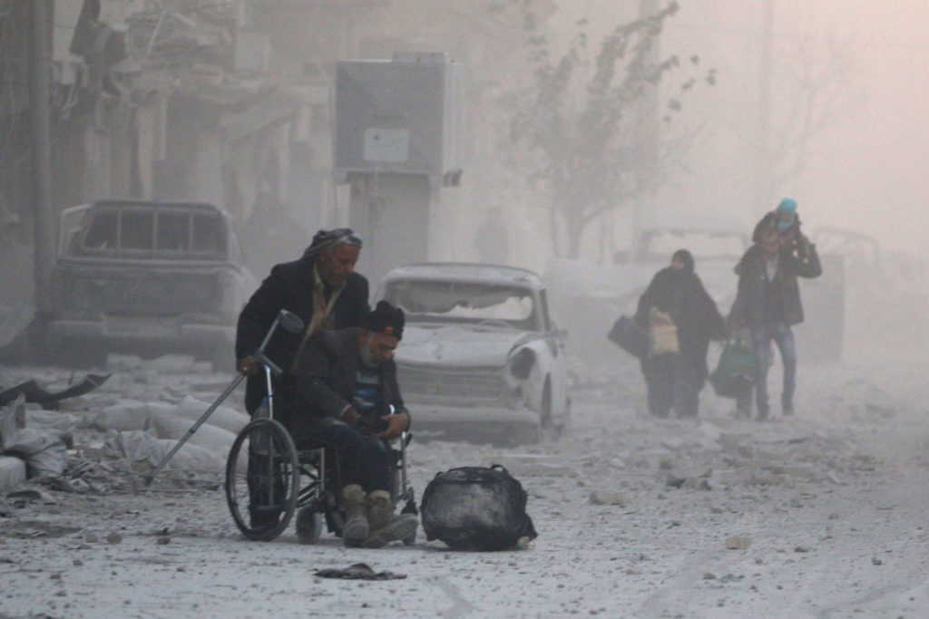 FILE PHOTO - A man on a wheelchair flees with others into the remaining rebel-held areas of Aleppo, Syria December 9, 2016. REUTERS/Abdalrhman Ismail /File Photo