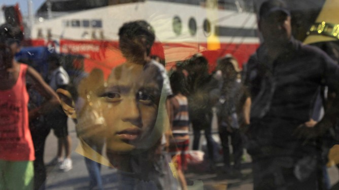 epa04990645 YEARENDER 2015 SEPTEMBER A child from Syria looks outside a bus as the ferry 'Eleftherios Venizelos' is reflected on it, after its arrival at port of Piraeus near Athens, Greece, carrying about 2500 Syrian refugees who landed on the Greek islands of Lesvos and Kos from Turkey, 04 September 2015.  EPA/ORESTIS PANAGIOTOU