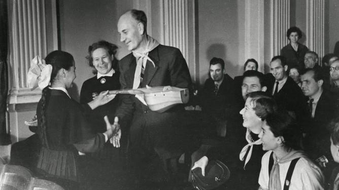 Fra statsminister Einar Gerhardsens offisielle besøk i Sovjetunionen, november 1955. Gerhardsen får overrakt en balalaika som gave av en ung pioner. Gerhardsen, Einar; Gerhardsen, Werna