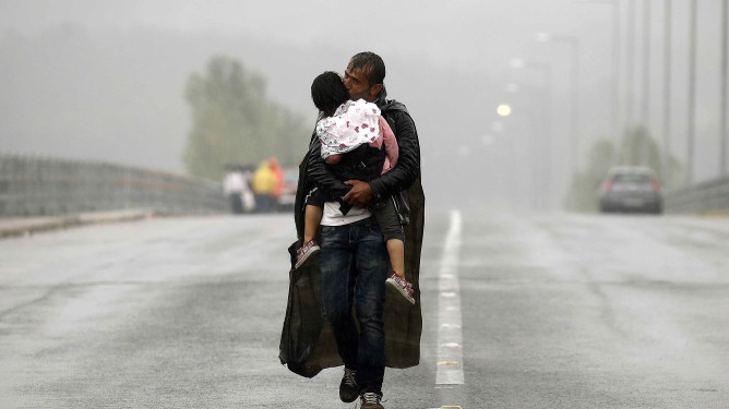 A Syrian refugee kisses his son as he walks through a rainstorm towards Greece's border with Macedonia, near the Greek village of Idomeni, September 10, 2015. Most of the people flooding into Europe are refes fleeing violence and persecution in their home countries who have a legal right to seek asylum, the United Nations said on Tuesday.  REUTERS/Yannis Behrakis