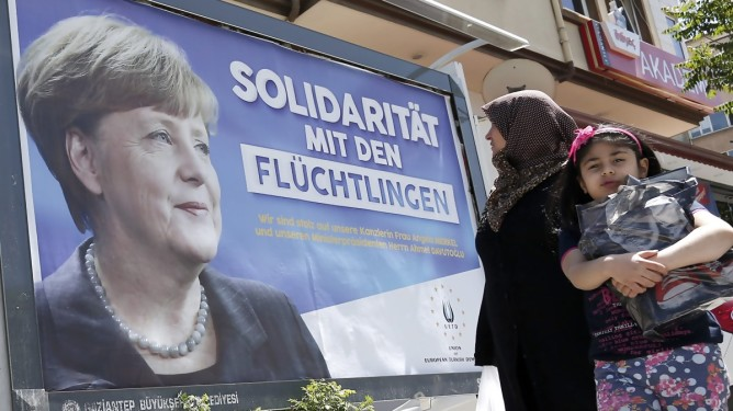 epa05273138 People walk in front of billboards with the picture of German Chancellor Angela Merkel with the words; 'Solidarity with the refugees', in Gaziantep, Turkey, 23 April 2016. German Chancellor Angela Merkel will visit refugee camps in Nizip district near Gaziantep on 23 April 2016.  EPA/SEDAT SUNA