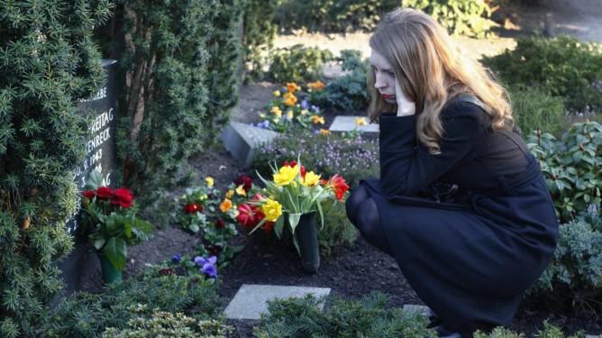 Kvinne ved grav på gravlund.