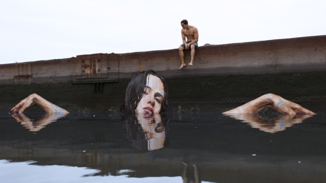 "Being able to paint lifelike murals is a talent in itself, let alone balancing on a paddleboard whilst doing so. Hawaii-born painter and street artist Sean Yoro, aka Hula, uses a paddleboard to access potential canvases. Once he finds a suitable surface, Yoro balances on his paddleboard while he patiently goes about transforming the canvas into a stunning piece of interactive art. Not only does Hula paint on walls, he has even painted a stunning mural on an iceberg. The artist used the water line as a frame and his figure is illustrated to appear as though it's emerging from the sea. Hula told website The Creators Project, âäœI painted my murals on melting icebergs as a representation of people already being affected by climate change and the need for urgency in responding.âä The fleeting condition of the mural, in that in a few weeks time they will melt, dissolve, and be lost forever, highlights the time sensitive nature of this issue. Yoro writes about the project on his website: âäœI hope they ignite a sense of urgency, as they represent the millions of people in need of our help who are already being affected from the rising sea levels of climate change.âä  For legal reasons, the locations of Hulaâä™s iceberg murals are undisclosed. Hula's current installation âä"" called Lewa âä"" is painted on an abandoned shipping dock and depicts a woman gently reclining as if at the edge of a swimming pool. You can find more of his work on Instagram under @the_hula where the artist has almost 100k followers. Featuring: Sean 'Hula' Yoro, Lewa When: 31 Jul 2016 Credit: Sean 'Hula' Yoro (Supplied by WENN.com)  **WENN does not claim any ownership including but not limited to Copyright, License in attached material. Fees charged by WENN are for WENN's services only, do not, nor are they intended to, convey to the user any ownership of Copyright, License in material. By publishing this material you expressly agree to indemnify, to hold WENN, its directors, shareholders, empl"