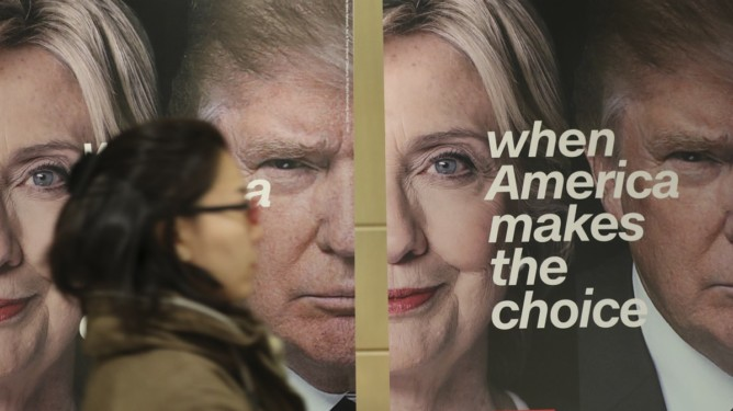 FILE - In this Wednesday, Nov. 9, 2016 photo, a woman walks by banners of Democratic presidential candidate Hillary Clinton and Republican presidential candidate Donald Trump during an election watch event hosted by the U.S. Embassy in Seoul, South Korea.  The United States headed for the polls to vote for their new president on Tuesday. (AP Photo/Lee Jin-man, File)