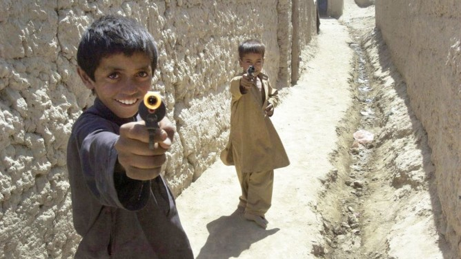 Boys playing with toy guns run into a village alley in Bagram, Afghanistan.