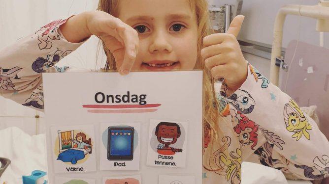 Bilde viser ei jente som holder opp en symboltavle. Jenta ser glad ut, og gir tommel opp.