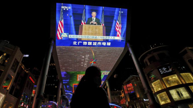 FILE - In this Nov. 8, 2020, file photo, a woman sells balloons near a giant TV screen broadcasting a news of U.S. President-elect Joe Biden delivers his speech, at a shopping mall in Beijing. (AP Photo/Andy Wong, File)