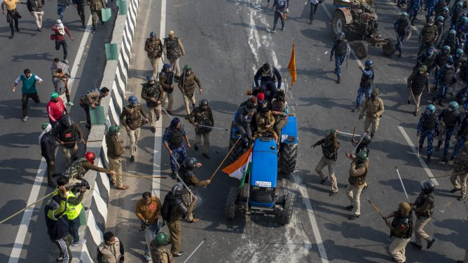 FILE - In this Tuesday, Jan.26, 2021, file photo, Indian policemen beat farmers driving a tractor towards the heart of the city as a sign of protest against new farm laws, during India's Republic Day celebrations in New Delhi, India. Following the farmer protests, the mainstream and social media have come under unprecedented attacks from Prime Minister Narendra Modi's Bharatiya Janata Party. The trigger for the clampdown was the death of a protester, Navneet Singh, when the largely peaceful rallies turned violent on Jan. 26 after a group of farmers veered from an agreed protest route and stormed New Delhi's 17th century Red Fort. Farmer leaders condemned the violence but refused to call off the protest. Authorities say no shots were fired and that Singh died because his tractor overturned. His family alleged he was fatally shot. (AP Photo/Altaf Qadri, File)