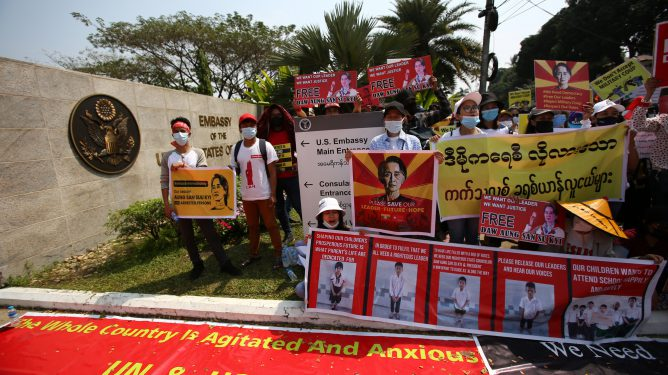 Anti-coup protesters gather outside the U.S. embassy in Yangon, Myanmar Friday, Feb. 19, 2021. A young woman who was shot in the head by police during a protest last week against the military's takeover of power in Myanmar died Friday morning, her brother said. (AP Photo)