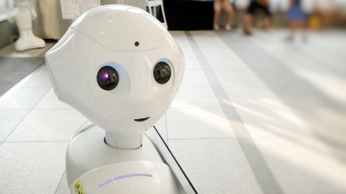 Bildet viser en hvit robot med menneskeaktige trekk. I bakgrunnen sitter en gruppe mennesker.