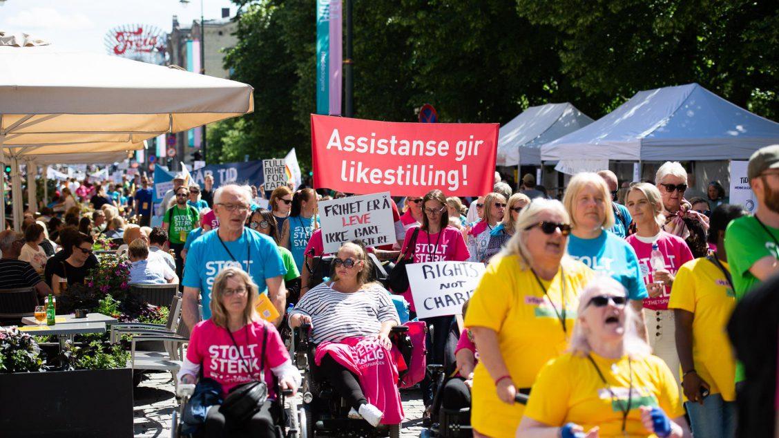 """Bilde fra Stolthetsparaden 2019, mange mennesker som går eller sitter i rullestol. Noen bærer faner med kamprop om likestilling. De fleste på bildet har på seg t-skjorter i gult, blått eller rosa hvor det står """"Stolt, sterk synlig"""""""